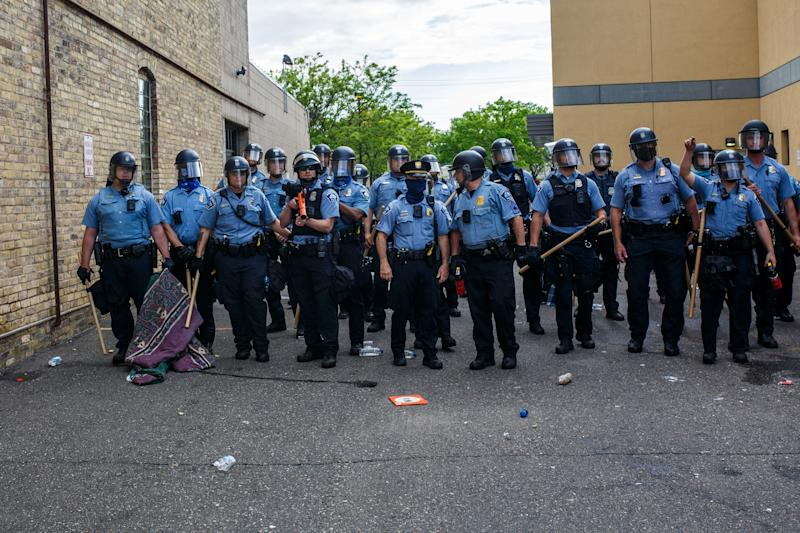 <strong>Police officers stand in a line while facing protesters demonstrating against the death of George Floyd outside the 3rd Precinct Police Precinct on May 27.</strong> (Photo: KEREM YUCEL via Getty Images)