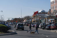 People cross the Rehoboth Avenue, Friday, Nov. 13, 2020, in Rehoboth Beach, Del. President-elect Joe Biden owns a $2.7 million, Delaware North Shores home with a swimming pool that overlooks Cape Henlopen State Park, is blocks from the ocean and a short drive from downtown Rehoboth Beach.(AP Photo/Alex Brandon)
