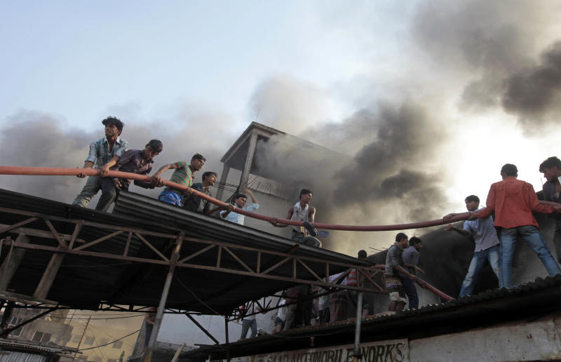 Bangladeshi firefighters and volunteers work to douse a fire at a two-storied garment factory in Dhaka, Bangladesh, Saturday, Jan.26, 2013. The fire killed at least six female workers and injured another five, police and fire officials said. The latest fire occurred more than two months after a deadly fire killed 112 workers in another factory near the capital city, raising questions about the safety measures in Bangladesh garment industry. (AP Photo/A.M. Ahad)