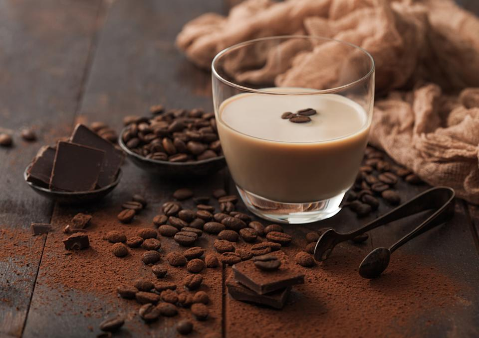 Glass of Irish cream baileys liqueur with ice cubes,coffee beans and powder with dark chocolate and brown cloth on dark wood background. Space for text