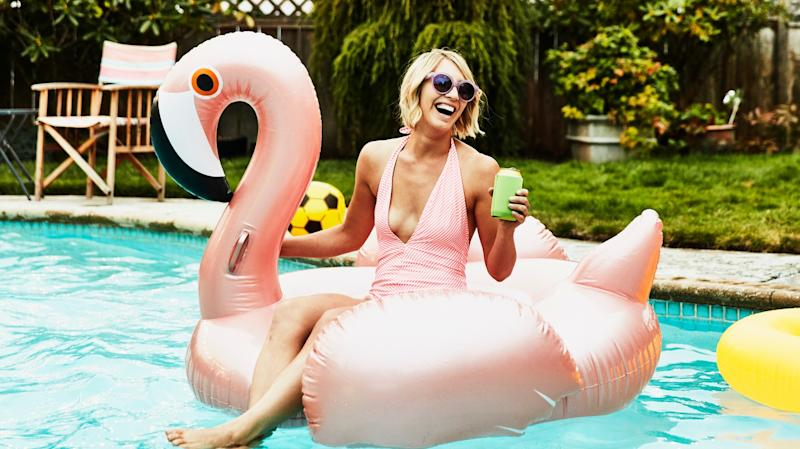 Laughing woman sitting on inflatable pool toy in backyard pool on summer evening.