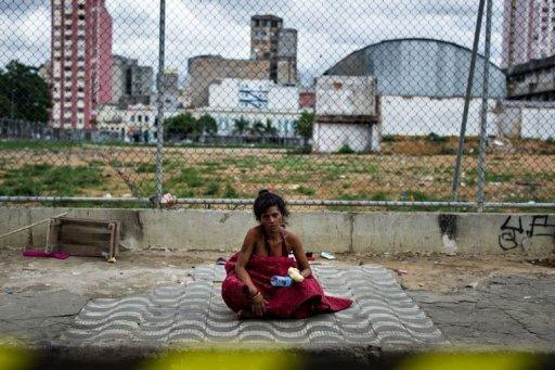 "A 40-year old homeless woman sits after receiving food provided by NGOs and social groups during their demonstration against military police's clean-up operation in the area called ""Cracolandia (Crackland in English)"" in downtown of Sao Paulo, Brazil, on January 14"