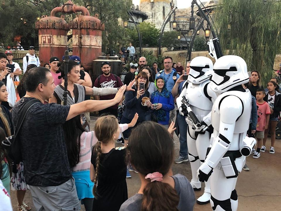 Rey leads a pack of guests to repel Stormtroopers in Star Wars: Galaxy's Edge