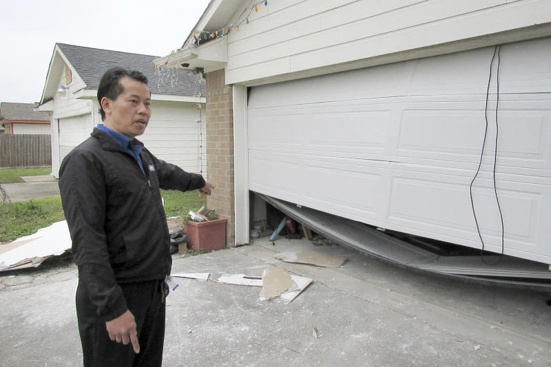 In this Thursday, Jan. 30, 2020 photo, Houston resident Quan Nguyen talks about the damage, including a twisted garage door, his home sustained after the Jan. 24, 2020, explosion at a nearby industrial business. Last month's explosion at a Houston metal fabricating and manufacturing company that killed two workers and damaged hundreds of structures has renewed debate over the city's lack of zoning.   (AP Photo/ Juan Lozano)