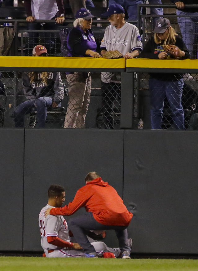 Philadelphia Phillies left fielder Aaron Altherr is looked at by a trainer after injuring himself on the wall during the fourth inning of a baseball game against the Colorado Rockies on Monday, Sept. 24, 2018, in Denver. (AP PhotoJack Dempsey)