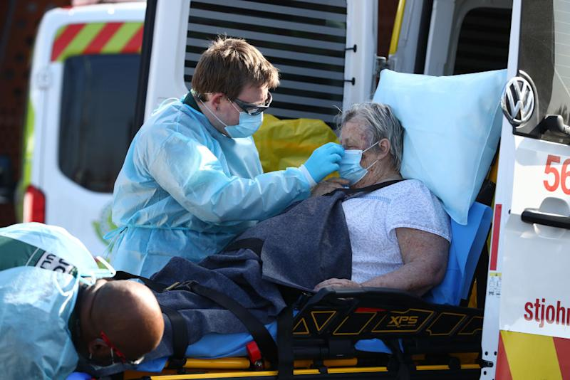 A nurse secures the mask of a female aged care home resident as she is moved into an ambulance.