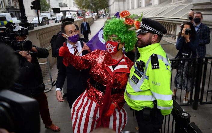 An actor dressed as a pantomime Dames poses for a photograph with a police officer, outside the gates to Downing Street, the official residence of Britain';s Prime Minister, as he takes part in a protest march towards the Houses of Parliament in London on September 30, 2020 - Ben Stansall/AFP