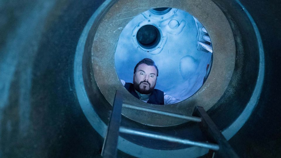 A goateed Jack Black looks out a circular window.