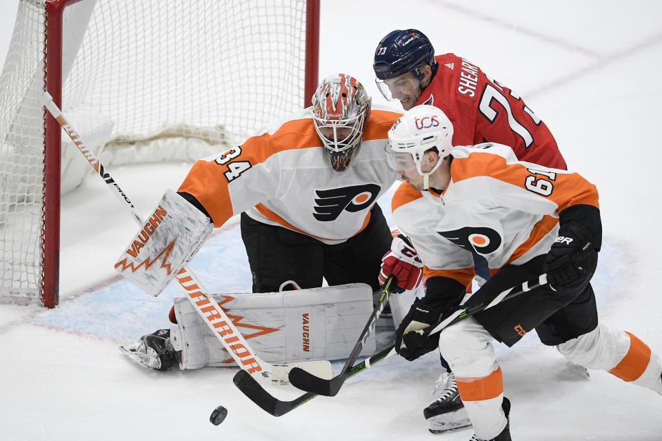 Philadelphia Flyers goaltender Alex Lyon (34) and defenseman Justin Braun (61) work for the puck against Washington Capitals left wing Conor Sheary (73) during the third period of an NHL hockey game Saturday, May 8, 2021, in Washington. The Capitals won 2-1 in overtime. (AP Photo/Nick Wass)