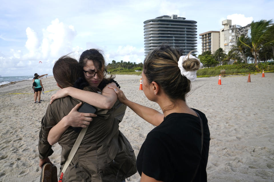 """Faydah Bushnaq, of Sterling, Va., center, is hugged by Maria Fernanda Martinez, of Boca Raton, Fla., as they stand outside of a 12-story beachfront condo building which partially collapsed, Friday, June 25, 2021, in the Surfside area of Miami. Bushnaq is vacationing and stopped to write """"Pray for their Souls"""" in the sand. (AP Photo/Lynne Sladky)"""