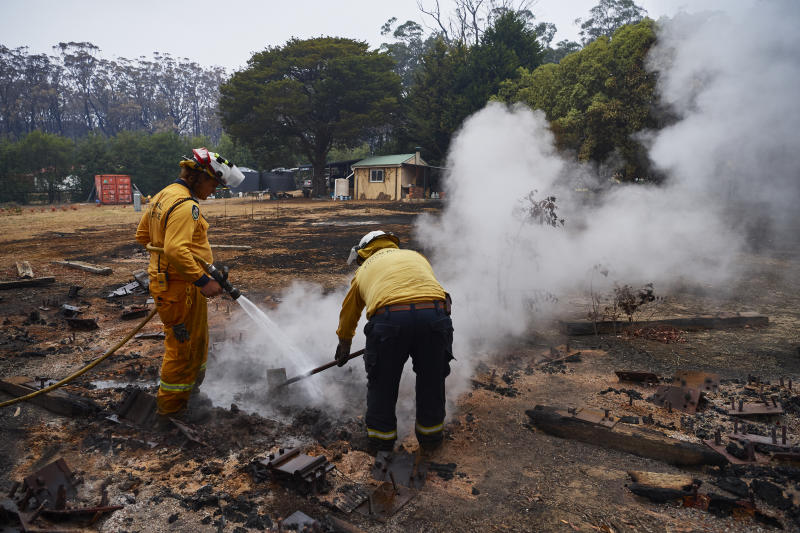 An RFS Crew attempts to put out a smouldering pile of railway sleepers in Wingello, Australia.