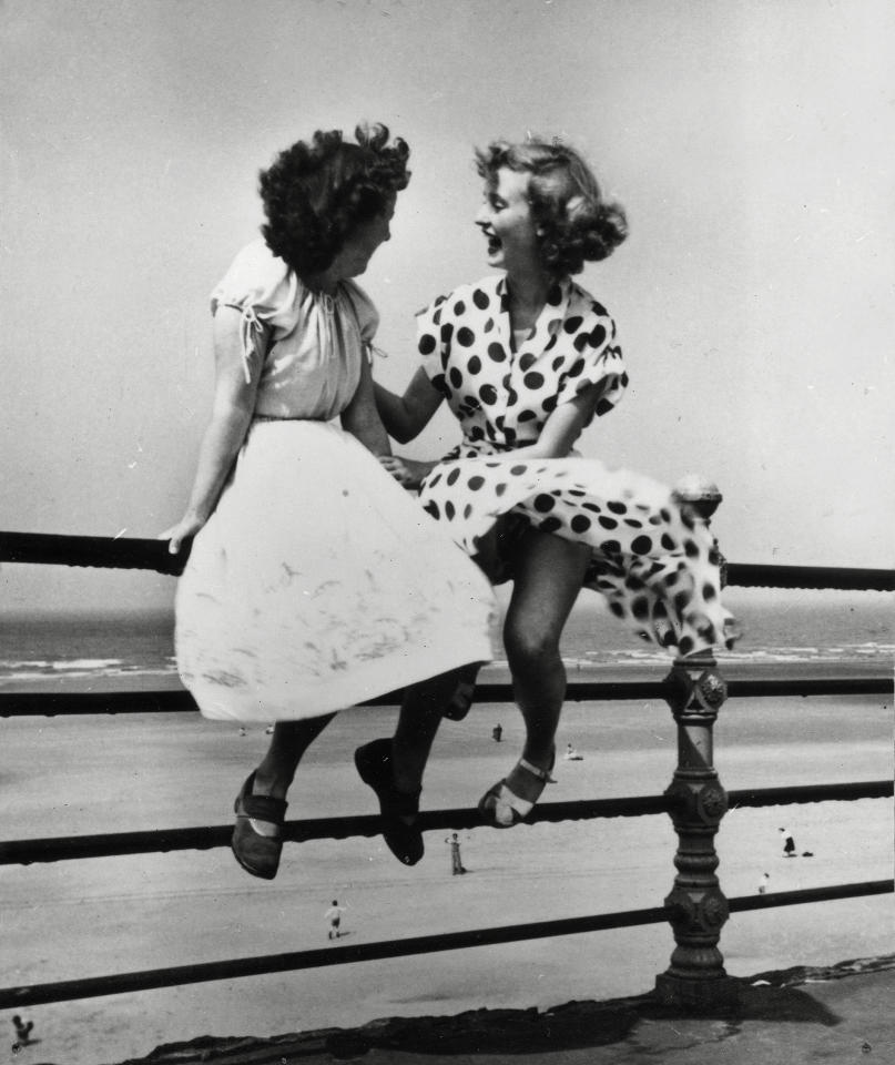 Two young women sit on a railing in Blackpool in 'Maidens in Waiting', 1951. This is one of Hardy's most recognisable images and captures a carefree post-War Britain (Bert Hardy/ Getty Images)