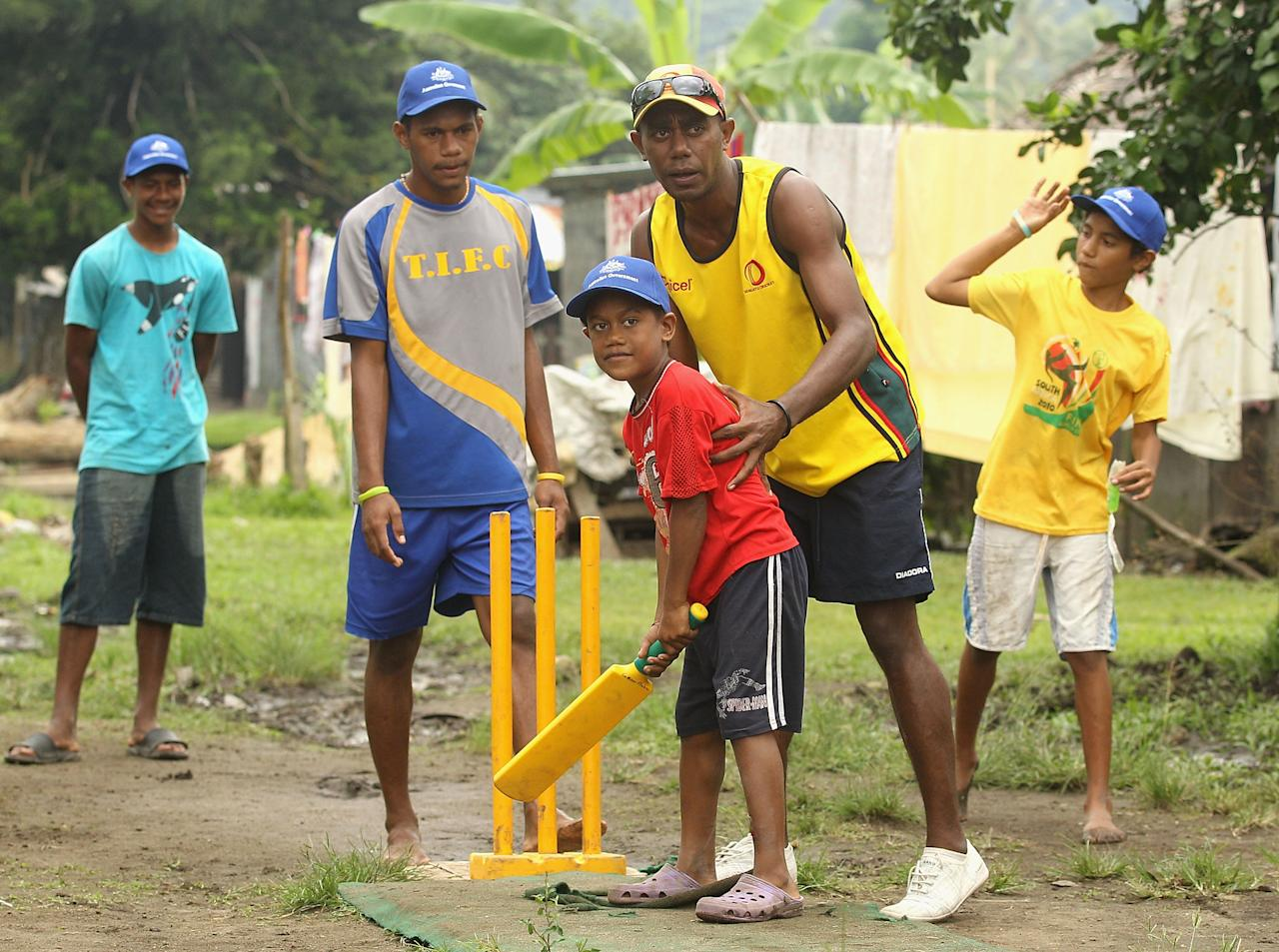 PORT VILA, VANUATU - MAY 16:  Local children play cricket with help from local instructors during an ICC Cricket Development Program Clinic in Mele Village on May 16, 2012 in Port Vila, Vanuatu.  (Photo by Hamish Blair/Getty Images)