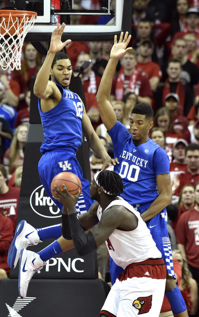 Kentucky's Karl-Anthony Towns, top left, and Marcus Lee, top right, contest a shot by Louisville's Montrezl Harrell during the first half of an NCAA college basketball game Saturday Dec. 27, 2014, in Louisville, Ky. Kentucky won 58-50. (AP Photo/Timothy D. Easley)