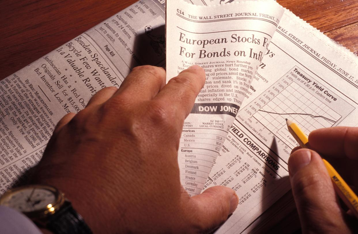 Hands Holding Financial Section Of Newspaper, Following Treasury Yield Curve. (Photo by Education Images/Universal Images Group via Getty Images)