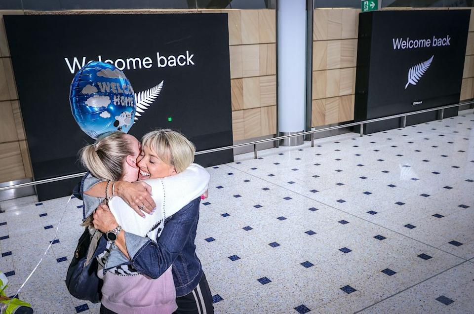 A passenger hugs a family member upon arrival from New Zealand at Sydney International Airport.