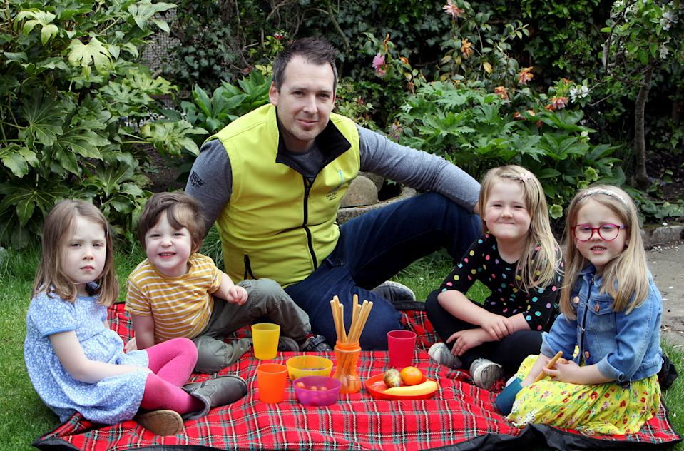 Sam Mills, 38, having a picnic with some of the children he looks after including his own son and daughter. (left-right) Molly (Sam's daughter) , Harry (Sam's son), Louisa and Catrin. [Photo: Caters]