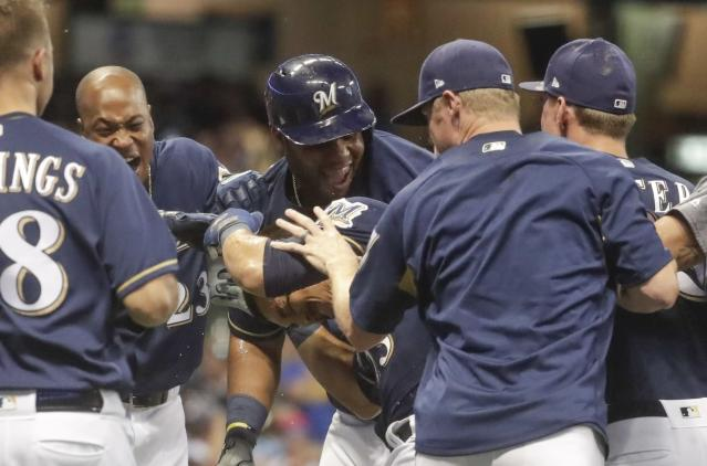 Milwaukee Brewers' Tyler Saladino is congratulated after hitting a walk-off sacrifice fly during the 10th inning of a baseball game against the Washington Nationals Tuesday, July 24, 2018, in Milwaukee. The Brewers won 5-4. (AP Photo/Morry Gash)