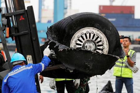 A worker assists his colleague during the lift up of a damaged tyre from Indonesian forensic policemen stand beside a damaged tyre from the the Lion Air flight JT610 jet, at Tanjung Priok port in Jakarta, Indonesia, November 5, 2018. REUTERS/Beawiharta/Files