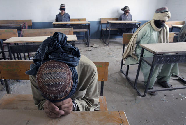 <p>A group of men detained for suspected Taliban activities are held for questioning at a schoolhouse in the village of Kuhak in Arghandab District, north of Kandahar July 9, 2010. (Photo: Bob Strong/Reuters) </p>