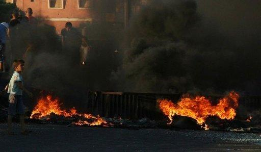 A Lebanese boy walks past burning tyres which Sunni Muslim residents of the town of al-Abdeh ignited