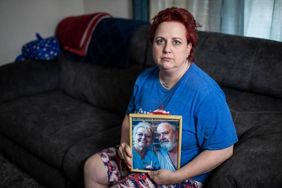 Kimberly Rhodus poses for a portrait holding a photograph of her father at her home in Richmond, Ky., Thursday, May 6, 2021. After her father died in 2016, his workers comp benefits were continuously deposited in their joint account for four years. Rhodus tried to figure out where the money was coming from, but was unable to come to a conclusion. Last year an official announced to Rhodus that she owed the state $56,000.