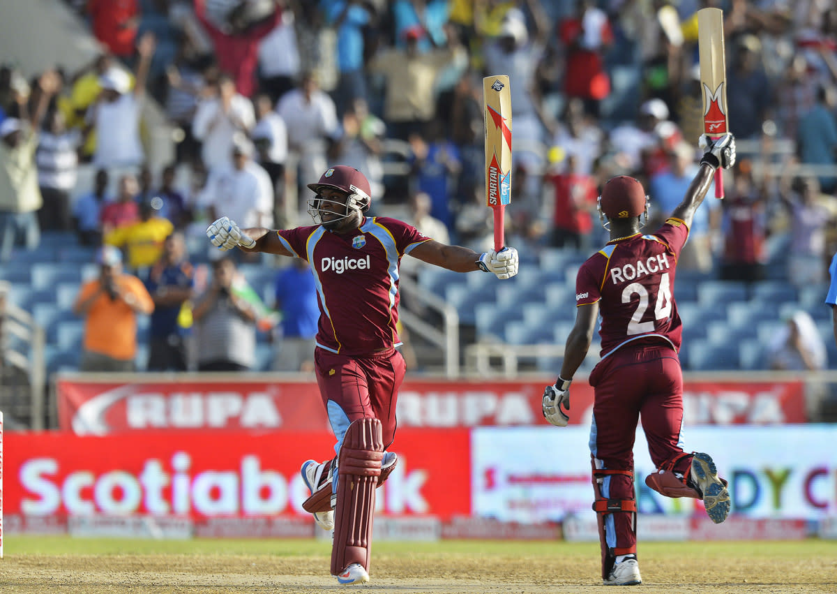 West Indies cricketers Kemar Roach (R) and Tino Best (L) celebrate taking the final run to defeat India during the second match of the Tri-Nation series between Indian and West Indies at the Sabina Park stadium in Kingston on June 30, 2013. West Indies defeated India by 1 wicket. AFP PHOTO/Jewel Samad