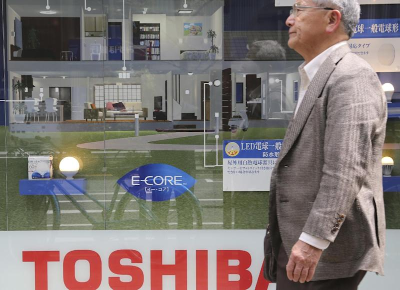 In this April 16, 2016 photo, a man walks past a display of Toshiba Corp.'s products in Tokyo. Japanese electronics and energy giant Toshiba delayed reporting its financial results by a month Tuesday, Feb. 14, 2017, citing problems with its auditing. Toshiba stock tumbled 8 percent in Tokyo trading after its earnings weren't announced as scheduled. The company said the earnings won't be out until March 14. Auditors had questioned Toshiba's reporting on the acquisition of CB&I Stone & Webster by its U.S. nuclear unit Westinghouse, the company said in a statement. (AP Photo/Koji Sasahara)