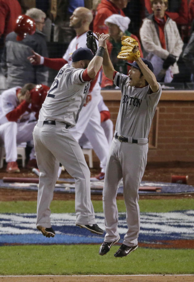 Boston Red Sox relief pitcher Koji Uehara and first baseman Mike Napoli (12) celebrate after Boston defeated the St. Louis Cardinals, 4-2, in Game 4 of baseball's World Series Sunday, Oct. 27, 2013, in St. Louis. (AP Photo/Charlie Riedel)