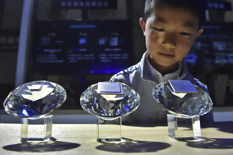 In this Sunday, May 26, 2019, photo released by Xinhua News Agency, a child looks at the chips designed for 5G base stations by Huawei on display at the China International Big Data Industry Expo 2019 in Guiyang, southwest China's Guizhou Province. China's latest media broadside in its trade war with the U.S. features an unlikely star: Trevor Noah of the Daily Show. The state broadcaster CCTV ran part of a segment from the show on Chinese equipment maker Huawei's dominance in 5G mobile technology in its lunchtime news show Monday, May 27. (Ou Dongqu/Xinhua via AP)