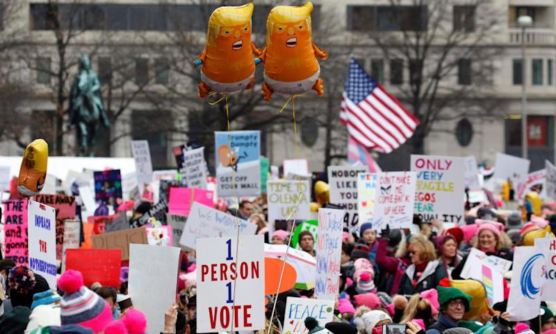 Baby Trump balloons float over thousands of people as they participate in the Women's March at Freedom Plaza in Washington DC.