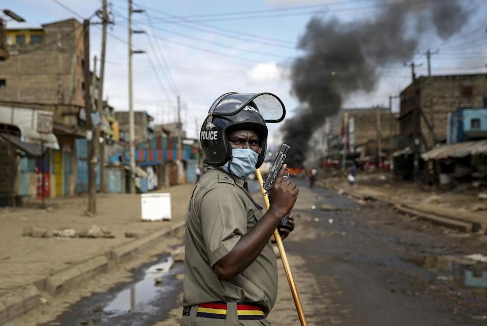An armed police officer during clashes with protesters near a barricade in the Kariobangi slum of Nairobi