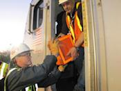 NTSB investigator Mike Hiller obtains the locomotive event data recorder from an Amtrak train involved in an accident in Philadelphia, Pennsylvania, in this handout photo provided by the National Transportation Safety Board, May 13, 2015. Federal investigators have recovered the black box from the wreckage of an Amtrak train that derailed in Philadelphia and were reviewing data to determine what caused the crash that killed at least six people and injured more than 200, officials said on Wednesday. REUTERS/NTSB/Handout FOR EDITORIAL USE ONLY. NOT FOR SALE FOR MARKETING OR ADVERTISING CAMPAIGNS. THIS IMAGE HAS BEEN SUPPLIED BY A THIRD PARTY. IT IS DISTRIBUTED, EXACTLY AS RECEIVED BY REUTERS, AS A SERVICE TO CLIENTS