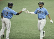 Tampa Bay Rays' Manuel Margot, left, congratulates Brandon Lowe, right, after Lowe's solo home run off New York Yankees starter James Paxton during the seventh inning of a baseball game Sunday, Aug. 9, 2020, in St. Petersburg, Fla. (AP Photo/Steve Nesius)