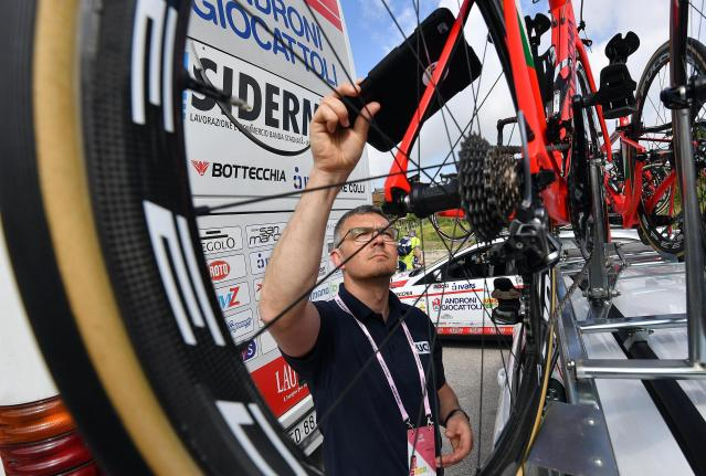 A UCI delegate scans a bike to check for motors prior to the start the 9th stage of the Giro dItalia cycling race from Pesco Sannita to Campo Imperatore, Italy, Sunday, May 13, 2018. Simon Yates cemented his position as overall leader of the Giro d'Italia by winning the ninth stage on Sunday but it was a bad day for British compatriot Chris Froome, who lost more than a minute in the general classification. (Daniel Dal Zennaro/ANSA via AP)