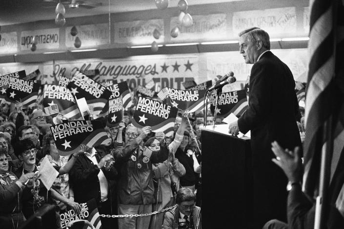 FILE - In this Wednesday, Oct. 14, 1984, file photo, a sign-waving crowd cheers Democratic presidential candidate Walter Mondale, right, as he delivers a campaign address at Victory Hall in the Milwaukee suburb of Cudahy, Wis. Campaign workers estimated 1,500 people packed the hall with another 1,000 outside. Mondale, a liberal icon who lost the most lopsided presidential election after bluntly telling voters to expect a tax increase if he won, died Monday, April 19, 2021. He was 93. (AP Photo/John Duricka, File)