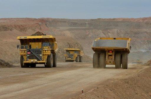 Trucks drive on a mine operated by Rio Tinto in Mongolia in June 2012