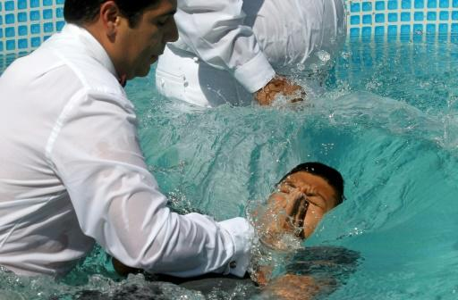 """Do you believe in Jesus Christ?"" a minister asked newly baptized members, who responded ""Amen!"" with their right hands raised before being plunged into the full-body baptismal pools"