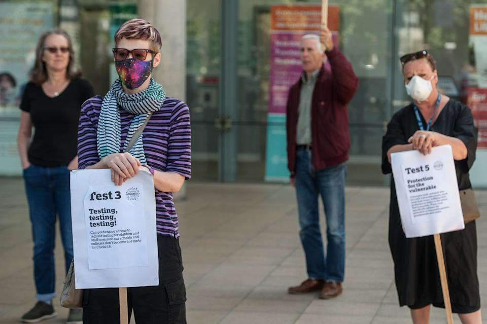 LONDON, ENGLAND - MAY 7: Members of the National Education Union (NEU) hold a socially distanced protest outside the Learning Trust in Hackney to demand that safety criteria demanded by their Trade Union is adhered to before schools reopen on May 7, 2020 in London, England. The UK is continuing with quarantine measures intended to curb the spread of Covid-19, but as the infection rate is falling government officials are discussing the terms under which it would ease the lockdown. (Photo by Guy Smallman/Getty Images)