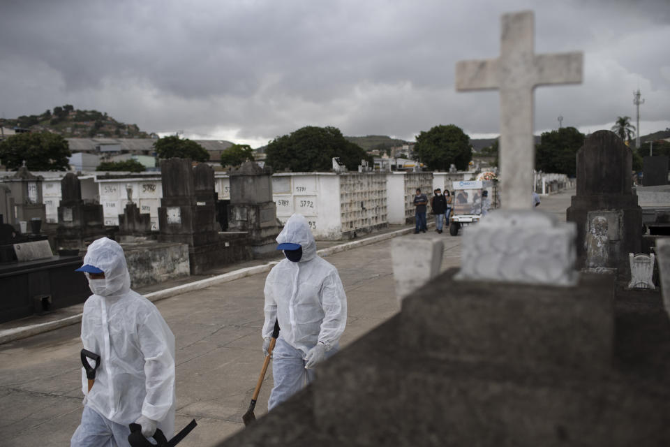 FILE - In this April 13, 2021, file photo, cemetery workers in protective gear walk to the burial of a woman who died from complications related to COVID-19 at the Inahuma cemetery in Rio de Janeiro, Brazil. The picture is still grim in parts of Europe and Asia as variants of the virus fuel an increase in new cases and the worldwide death toll closes in on 3 million. (AP Photo/Silvia Izquierdo, File)