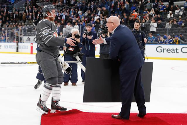 Edmonton Oilers forward Connor McDavid, left, accepts the winning team's check after the Pacific Division defeated the Atlantic Division 5-4 in the NHL hockey All Star final game Saturday, Jan. 25, 2020, in St. Louis. (AP Photo/Jeff Roberson)