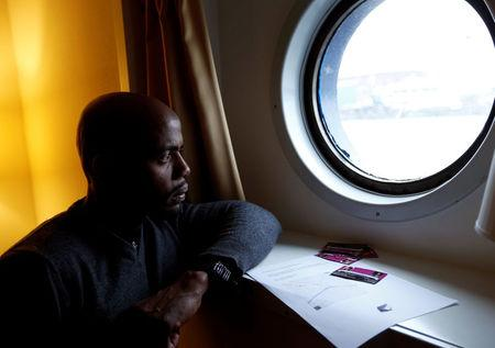 Sall from Guinea looks through a window of a boat cabin in a floating hotel in Groningen