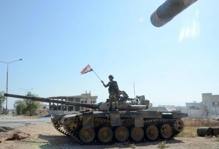 A Syrian soldier waves a national flag atop a tank in the strategic town of Khan Sheikhun on Saturday