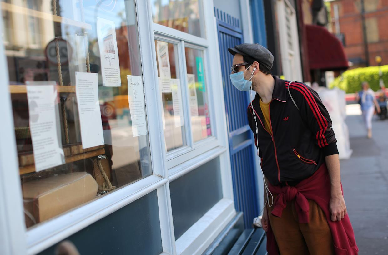 A man wearing PPE (personal protective equipment), including a face mask as a precautionary measure against COVID-19, looks at the window notice informing customers that Chamomile Cafe is closed to mitigate the spread of COVID-19, at Englands Lane in north London on May 19, 2020. - England's Lane is one of those postcard streets in London just a short walk from Primerose Hill Park. But behind the colourful facades, the shops have had their darkest hours - and varying fortunes - in the face of the coronavirus pandemic. (Photo by ISABEL INFANTES / AFP) / TO GO WITH AFP STORY BY VERONIQUE DUPONT (Photo by ISABEL INFANTES/AFP via Getty Images)