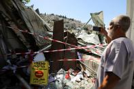 A Palestinian man uses his mobile phone as he stands near the debris of a shop that Israel demolished in the Palestinian neighbourhood of Silwan in East Jerusalem
