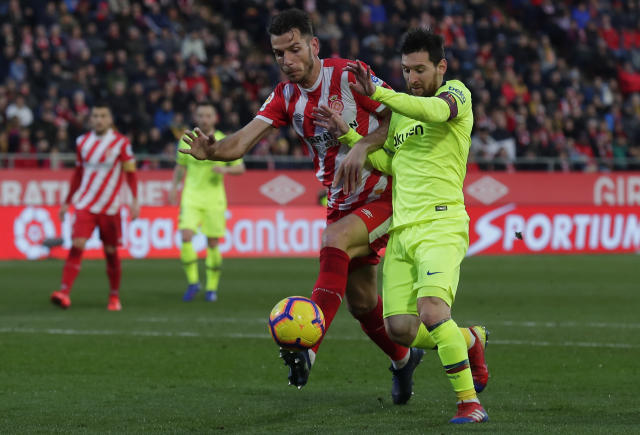 FC Barcelona's Lionel Messi, right, duels for the ball with Girona's Pedro Alcala during the Spanish La Liga soccer match between Girona and FC Barcelona at the Montilivi stadium in Girona, Spain, Sunday, Jan. 27, 2019. (AP Photo/Manu Fernandez)