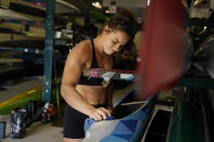 Canoe sprint world champion Nevin Harrison, 19, of Seattle, cleans her boat before she trains near Lake Lanier Olympic Park on Thursday, July 1, 2021, in Gainesville, Ga. Harrison won the world championship in the women's sprint canoe 200 meters as a 17-year-old in 2019. Now she'll try to duplicate that at the Olympics in Tokyo where the race will be a new event in a bid for gender equity. (AP Photo/Brynn Anderson)