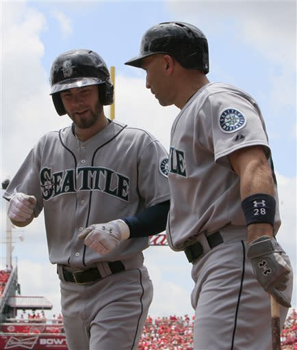 Seattle Mariners' Nick Franklin, left, is congratulated by teammate Raul Ibanez, right, after hitting a solo home run off Cincinnati Reds starting pitcher Bronson Arroyo in the first inning during a baseball game on Sunday, July 7, 2013, in Cincinnati. (AP Photo/David Kohl)