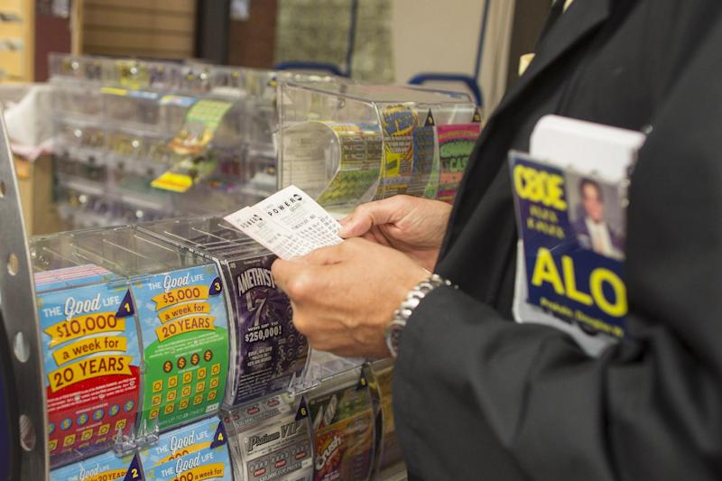 Douglas Priskalo purchases Powerball tickets at a convenience store in Chicago, Wednesday, Aug. 7, 2013. Ticketholders are hoping to win Wednesday's Powerball drawing, estimated at $425 million so far. (AP Photo/Scott Eisen)