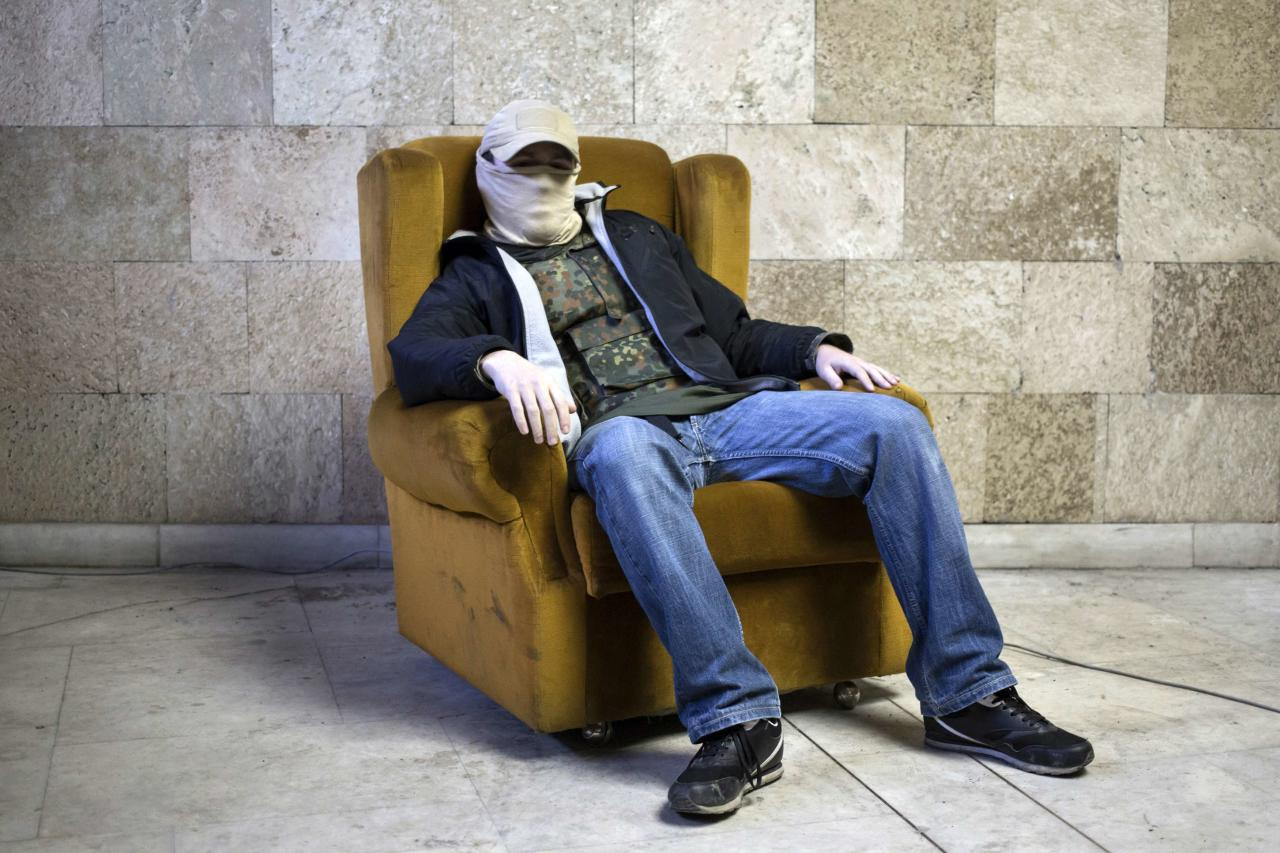 A masked pro-Russian protester sits on a chair as he poses for a picture inside a regional government building in Donetsk, eastern Ukraine April 25, 2014. Picture taken April 25, 2014. REUTERS/Marko Djurica (UKRAINE - Tags: CIVIL UNREST POLITICS PORTRAIT)